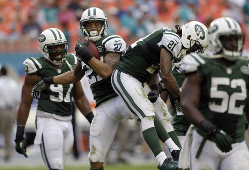 New York Jets cornerback Dee Milliner (27) celebrates with teammates after intercepting a pass by Miami Dolphins quarterback Ryan Tannehill during the fourth quarter of an NFL football game in Miami Gardens, Fla., Sunday, Dec. 29, 2013. The Jets won 20-7. (AP Photo/Alan Diaz)