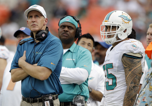 Miami Dolphins head coach Joe Philbin, left, and outside linebacker Koa Misi (55) watch in the final minutes of an NFL football game against the New York Jets, Sunday, Dec. 29, 2013, in Miami Gardens, Fla. The Jets defeated the Dolphins 20-7.  (AP Photo/Lynne Sladky)