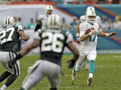 Miami Dolphins quarterback Ryan Tannehill (17) runs against the New York Jets during the third quarter of an NFL football game Sunday, Dec. 29, 2013, in Miami Gardens, Fla. (AP Photo/Alan Diaz)