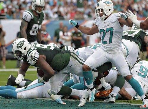 New York Jets defensive end Sheldon Richardson (91), playing offense, breaks through the Miami Dolphins defense, including defensive back Jimmy Wilson (27) to score on a one-yard touchdown run during the second quarter of an NFL football game Sunday, Dec. 29, 2013, in Miami Gardens, Fla. (AP Photo/Lynne Sladky)