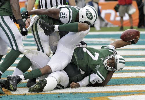 New York Jets quarterback Geno Smith (7) celebrates after diving into the end zone to score on a 7-yard touchdown run in the second quarter of an NFL football game against the Miami Dolphins Sunday, Dec. 29, 2013, in Miami Gardens, Fla. (AP Photo/Alan Diaz)