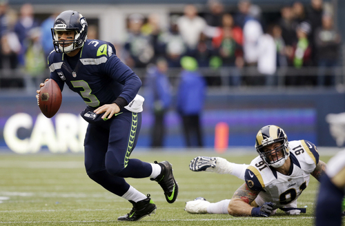 Seattle Seahawks quarterback Russell Wilson (3) scrambles away from St. Louis Rams' Chris Long in the first half of an NFL football game, Sunday, Dec. 29, 2013, in Seattle. (AP Photo/Elaine Thompson)
