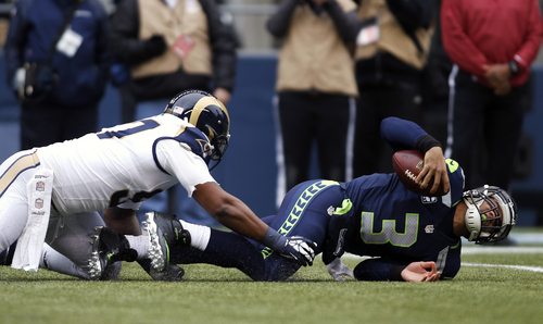 Seattle Seahawks quarterback Russell Wilson (3) is sacked by St. Louis Rams defensive end Eugene Sims, left, in the first half of an NFL football game, Sunday, Dec. 29, 2013, in Seattle. (AP Photo/John Froschauer)
