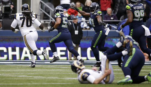 Seattle Seahawks outside linebacker Malcolm Smith, second from left, runs an interception for a touchdown as St. Louis Rams quarterback Kellen Clemens, front, is on the ground and Rams' Brandon Washington, left, pursues, in the first half of an NFL football game, Sunday, Dec. 29, 2013, in Seattle. (AP Photo/Elaine Thompson)
