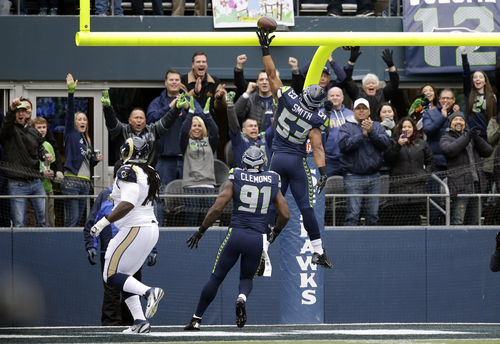 Fans cheer as Seattle Seahawks outside linebacker Malcolm Smith (53) spikes the ball over the goal post as Seahawks' Chris Clemons (91) is near after Smith ran an interception for a touchdown against the St. Louis Rams in the first half of an NFL football game, Sunday, Dec. 29, 2013, in Seattle. (AP Photo/Elaine Thompson)