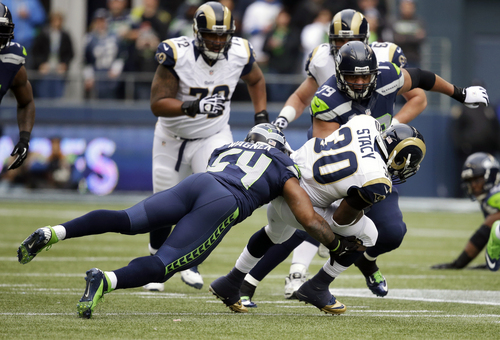 Seattle Seahawks middle linebacker Bobby Wagner (54) tackles St. Louis Rams' Zac Stacy (30) as Seahawks' Red Bryant (79) closes in during the first half of an NFL football game, Sunday, Dec. 29, 2013, in Seattle. (AP Photo/Elaine Thompson)