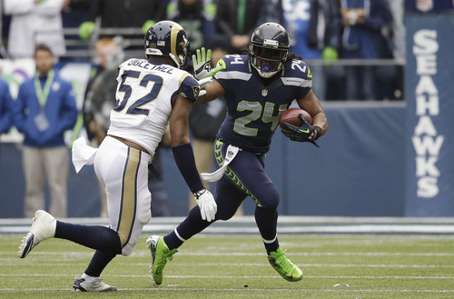 Seattle Seahawks running back Marshawn Lynch (24) rushes against St. Louis Rams outside linebacker Alec Ogletree (52) in the first half of an NFL football game, Sunday, Dec. 29, 2013, in Seattle. (AP Photo/Elaine Thompson)