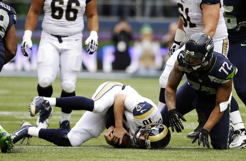 St. Louis Rams quarterback Kellen Clemens (10) rolls over after he was sacked by Seattle Seahawks defensive end Michael Bennett (72) in the first half of an NFL football game, Sunday, Dec. 29, 2013, in Seattle. (AP Photo/Elaine Thompson)