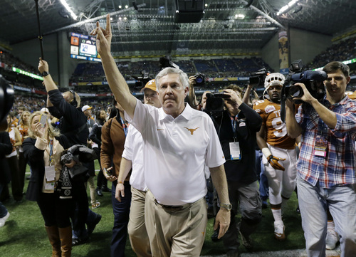 """Eric Gay   The Associated Press Texas coach Mack Brown, center, holds up the """"Hook' em Horns"""" sign as he sings the school song following the Valero Alamo Bowl NCAA college football game against Oregon, Monday,  Dec. 30, 2013, in San Antonio. Oregon won 30-7. (AP Photo/Eric Gay)"""
