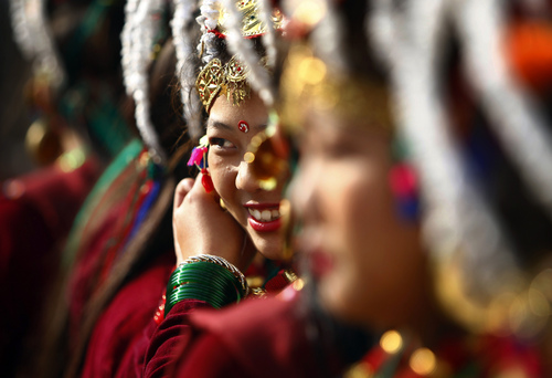"A Nepalese Gurung community woman in traditional attire smiles as she dances during Tamu Loshar in Katmandu, Nepal, Monday, Dec. 30, 2013. Tamu Loshar is the New Year of the Gurung community, an indigenous community who also call themselves ""Tamu."" (AP Photo/Niranjan Shrestha)"