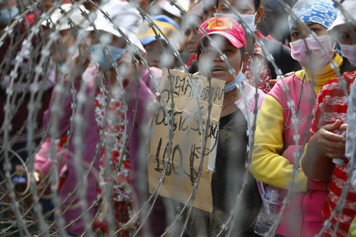 Cambodian garment workers shout slogans behind barbed wire set up by police near the Council of Ministers building during a rally in Phnom Penh, Cambodia, Monday, Dec. 30, 2013. The workers are demanding doubling their monthly salary to US$160 from $80. (AP Photo/Heng Sinith)