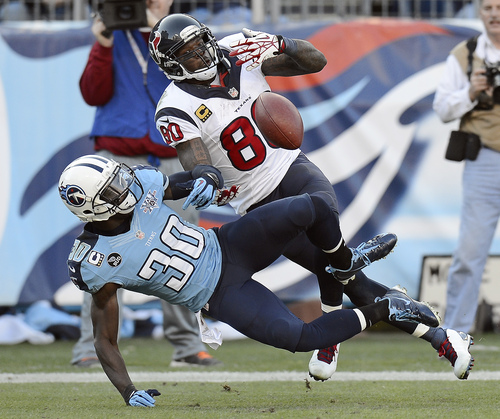 Tennessee Titans cornerback Jason McCourty (30) breaks up a pass intended for Houston Texans wide receiver Andre Johnson (80) in the fourth quarter of an NFL football game Sunday, Dec. 29, 2013, in Nashville, Tenn. (AP Photo/Mark Zaleski)