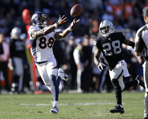 Denver Broncos wide receiver Demaryius Thomas (88) catches a 63-yard touchdown pass from quarterback Peyton Manning past Oakland Raiders defensive back Phillip Adams (28) during the second quarter of an NFL football game, Sunday, Dec. 29, 2013, in Oakland, Calif. With this score, the Broncos surpassed the 2007 New England Patriots for the most points scored in a season. (AP Photo/Marcio Jose Sanchez)