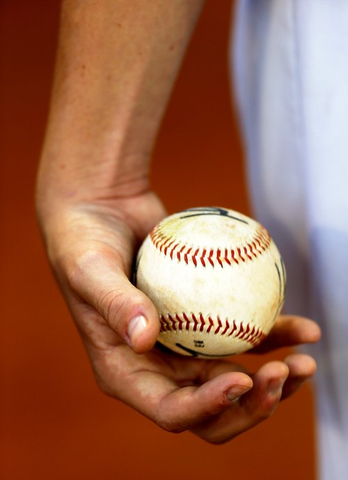 In this Nov. 27, 2013 photo, Tiburones of La Guaira's Anthony DeFrancesco of the U.S., tosses a baseball in his hand prior to a baseball game against rival Leones at Estadio Universitario in Caracas, Venezuela. It's about two months before pitchers and catchers report to spring training in the U.S., but in Venezuela the nation's fiercely competitive professional league is in full swing, and it's drawn the biggest contingent of American players in decades. (AP Photo/Fernando Llano)