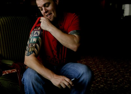 """In this Dec. 5, 2013 photo, C.J. Retherford, nicknamed """"El Conejo,"""" or """"the Rabbit,"""" shows off his tattoo with a rabbit hiding behind baby blocks spelling his 1-year-old son's name, Walker, during an interview at a hotel in Caracas, Venezuela. More than 5,000 followers on Twitter attest to the 28-year-old Arizona native's popularity among Venezuelan fans, who call him """"El Conejo,"""" as much for his protruding teeth as for the luck provided by his hot bat. Fawning female fans approach him for autographs when he leaves his Caracas hotel, but he says the star treatment was more intense in Barquisimeto, where he played last season for the Cardinals. (AP Photo/Fernando Llano)"""