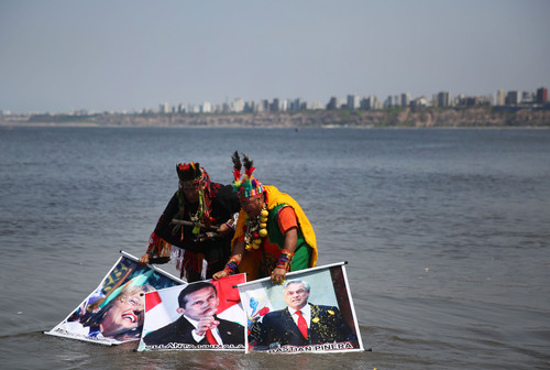 Shamans perform a good luck ritual to bring in the new year as they hold posters of Chile's President-elect Michelle Bachelet, left, Peru's President  Ollanta Humala, center, Chile's President Sebastian Piñera at the beach in Lima, Peru, Monday, Dec. 30, 2013. The shamans hope that this ritual will help Peru achieve a favorable result in its maritime dispute with Chile. (AP Photo/Martin Mejia)