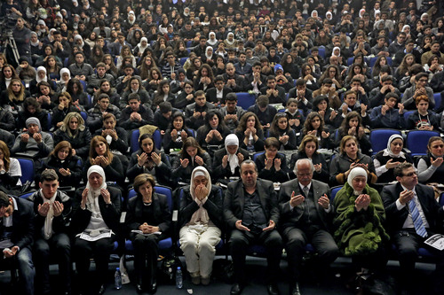 Lebanese parents, students, and teachers of the private Hariri High School, named after a prominent assassinated Sunni leader, pray for 16-year-old Mohammed Shaar, who was one of seven people killed in a car bomb that ripped through the upscale downtown district of Beirut, during a memorial ceremony, in Beirut, Lebanon, Monday, Dec. 30, 2013. The teenager in the red hoodie, black glasses and scruffy hair gazed in the group selfie on a sunny day in the upscale, downtown district of Beirut. It was the last image of Shaar. He was next captured as a lifeless strewn body, his red top and blood forming a scarlet blur on the pavement: an anonymous civilian casualty of a car-rigged bomb that killed a prominent politician and six others on Friday. (AP Photo/Bilal Hussein)