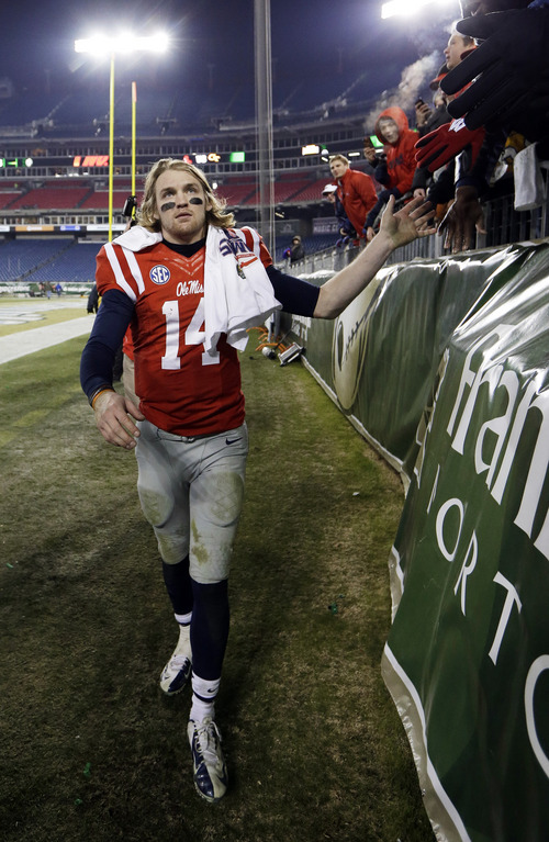Mississippi quarterback Bo Wallace slaps hands with fans as he leaves the field after beating Georgia Tech in the Music City Bowl on Monday, Dec. 30, 2013, in Nashville, Tenn. Mississippi won 25-17. (AP Photo/Mark Humphrey)