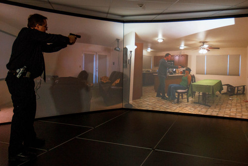Trent Nelson  |  The Salt Lake Tribune Unified Police Range Master Nick Roberts confronts a man holding a gun to a female hostage's head demonstrating a new five-screen training simulator used to put officers through realistic situations in Salt Lake City, Thursday November 7, 2013.