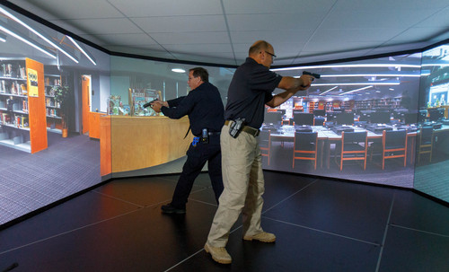 Trent Nelson  |  The Salt Lake Tribune Unified Police Deputy Chief Shane Hudson, right, and Range Master Nick Roberts run through a school shooting simulation while demonstrating a new five-screen training simulator used to put officers through realistic situations in Salt Lake City, Thursday November 7, 2013.