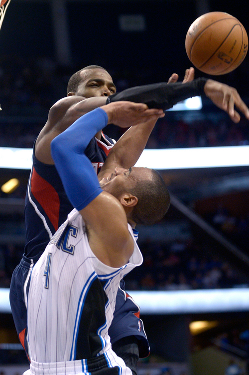 Orlando Magic guard Arron Afflalo (4) is fouled by Atlanta Hawks forward Paul Millsap while going up for a shot during the second half of an NBA basketball game in Orlando, Fla., Sunday, Dec. 29, 2013. The Magic won 109-102. (AP Photo/Phelan M. Ebenhack)