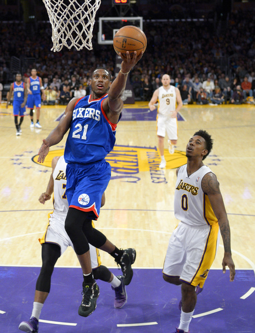 Philadelphia 76ers forward Thaddeus Young, left, puts up a shot as Los Angeles Lakers forward Nick Young defends during the first half of an NBA basketball game, Sunday, Dec. 29, 2013, in Los Angeles. (AP Photo/Mark J. Terrill)