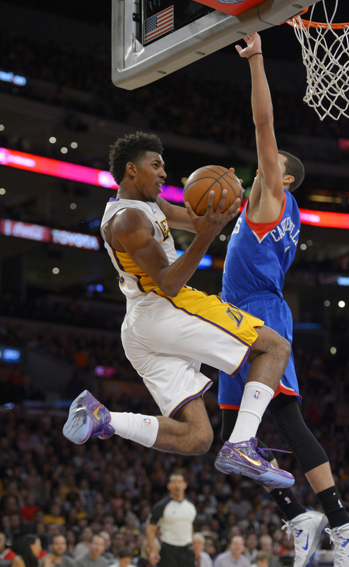 Los Angeles Lakers forward Nick Young, left, puts up a shot as Philadelphia 76ers guard Michael Carter-Williams defends during the first half of an NBA basketball game, Sunday, Dec. 29, 2013, in Los Angeles. (AP Photo/Mark J. Terrill)