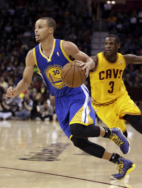 Golden State Warriors' Stephen Curry, left, drives around Cleveland Cavaliers' Dion Waiters (3) during the third quarter of an NBA basketball game, Sunday, Dec. 29, 2013, in Cleveland. Curry scored a team-high 29 points for the Warriors 108-104 win in overtime. (AP Photo/Tony Dejak)
