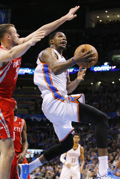 Oklahoma City Thunder forward Kevin Durant, right, goes to the basket in front of  Houston Rockets forward Chandler Parsons, left, during the third quarter of an NBA basketball game, Sunday, Dec. 29, 2013, in Oklahoma City. Oklahoma City won 117-86. (AP Photo/Alonzo Adams)