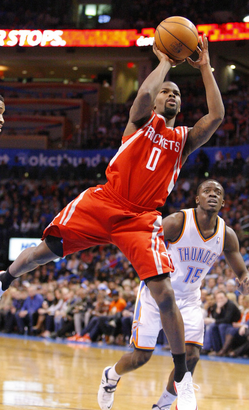 Houston Rockets guard Aaron Brooks, left, shoots in front of Oklahoma City Thunder guard Reggie Jackson, right, during the first quarter of an NBA basketball game, Sunday, Dec. 29, 2013, in Oklahoma City. (AP Photo/Alonzo Adams)