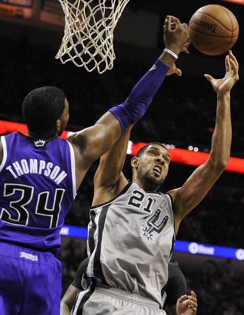 San Antonio Spurs forward Tim Duncan, right, chases a rebound against Sacramento Kings forward Jason Thompson during the second half of an NBA basketball game on Sunday, Dec. 29, 2013, in San Antonio. San Antonio won 112-104. (AP Photo/Darren Abate)