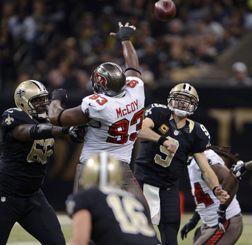 New Orleans Saints quarterback Drew Brees (9) passes as guard Ben Grubbs (66) blocks out a leaping Tampa Bay Buccaneers defensive tackle Gerald McCoy (93) during the first half of an NFL football game, Sunday, Dec. 29, 2013, in New Orleans. (AP Photo/Bill Feig)