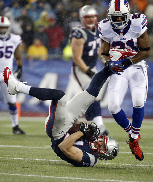 New England Patriots wide receiver Julian Edelman (11) lands after making a catch in front of Buffalo Bills cornerback Leodis McKelvin (21) in the second quarter of an NFL football game, Sunday, Dec. 29, 2013, in Foxborough, Mass. (AP Photo/Elise Amendola)