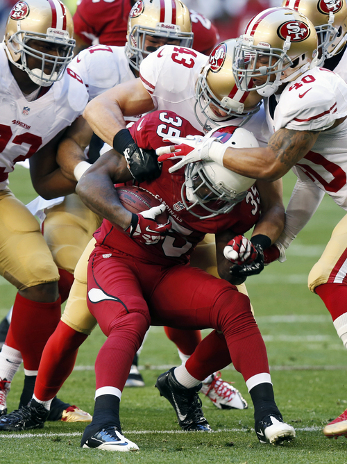 Arizona Cardinals cornerback Javier Arenas (35) is stopped by San Francisco 49ers' Darryl Morris (40), Craig Dahl (43) and Demarcus Dobbs during the first half of an NFL football game, Sunday, Dec. 29, 2013, in Glendale, Ariz.  (AP Photo/Ross D. Franklin)