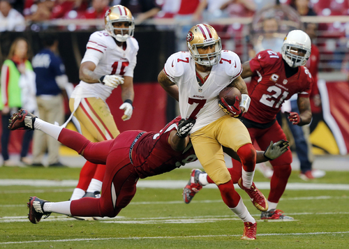 San Francisco 49ers quarterback Colin Kaepernick (7) breaks free of the tackle by Arizona Cardinals defensive end Calais Campbell during the second half of an NFL football game, Sunday, Dec. 29, 2013, in Glendale, Ariz. The 49ers won 23-20. (AP Photo/Rick Scuteri)