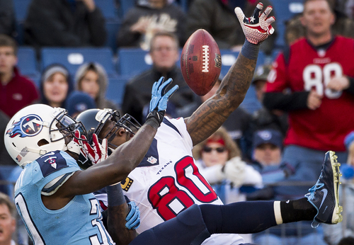 Tennessee Titans cornerback Jason McCourty, left, breaks up a pass in the end zone intended for Houston Texans wide receiver Andre Johnson (80) during the second half of an NFL football game on Sunday, Dec. 29, 2013, in Nashville, Tenn. (AP Photo/Houston Chronicle, Smiley N. Pool) MANDATORY CREDIT