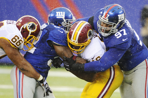 New York Giants defensive tackle Linval Joseph (97) and linebacker Jon Beason (52) tackles Washington's Alfred Morris during the first half of an NFL football game Sunday, Dec. 29, 2013, in East Rutherford, N.J.  Washington's Chris Chester (66) moves in on the play. (AP Photo/Bill Kostroun)