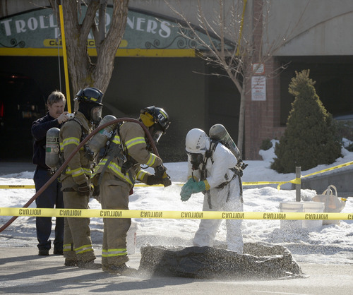 Al Hartmann  |  The Salt Lake Tribune Salt Lake City Fire Department hoses off a member of Hazardous Materials Response Team investigating a possible ricin letter sent to radio stations at Trolley Corners buiding at 700 East and 550 South Monday December 30.