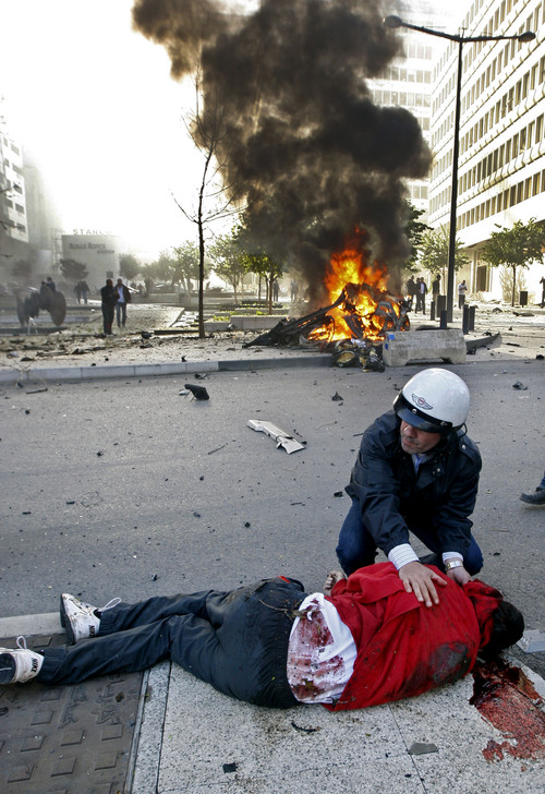 In this Friday, Dec. 27, 2013 photo, a Lebanese policeman helps 16-year-old Mohammed Shaar who was injured at the scene after a car bomb explosion in Beirut, Lebanon. The teenager in the red hoodie, black glasses and scruffy hair gazed in the group selfie on a sunny day in the upscale, downtown district of Beirut. It was the last image of Shaar. He was next captured as a lifeless strewn body, his red top and blood forming a scarlet blur on the pavement: an anonymous civilian casualty of a car-rigged bomb that killed a prominent politician and six others on Friday. (AP Photo)