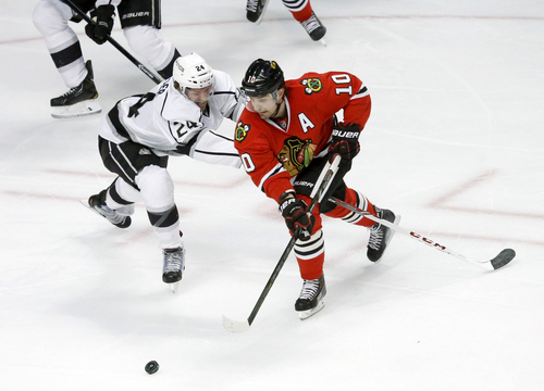Chicago Blackhawks left wing Patrick Sharp (10) skates towards the goal as Los Angeles Kings center Colin Fraser (24) defends during the first period of an NHL hockey game Monday, Dec. 30, 2013, in Chicago. (AP Photo/Charles Rex Arbogast)