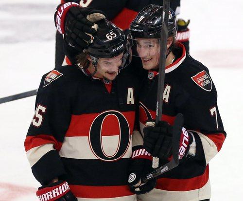 Ottawa Senators Erik Karlsson (65) and teammate Kyle Turris (7) celebrate after defeating the Washington Capitals 3-1 in Ottawa, Ontario, on Monday, Dec. 30, 2013. (AP Photo/The Canadian Press, Fred Chartrand)