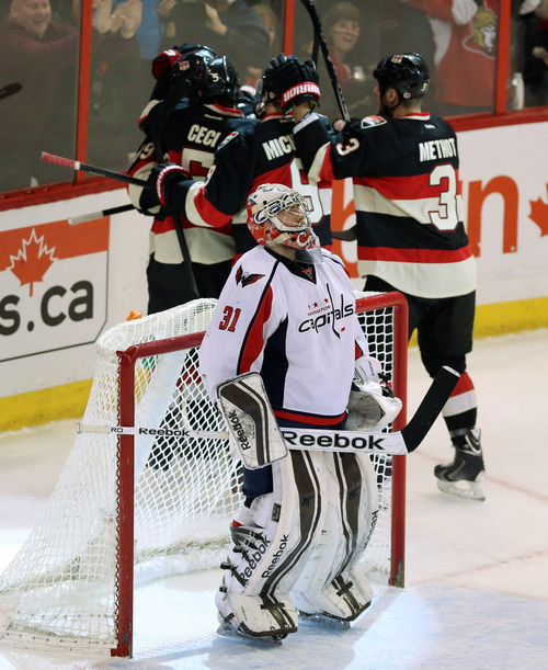 Washington Capitals goaltender Philipp Grubuer (31) reacts as members of the Ottawa Senators celebrate a goal during first period NHL hockey action in Ottawa, Ontario,  on Monday, Dec. 30, 2013.(AP Photo/The Canadian Press, Fred Chartrand)