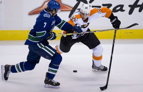 Vancouver Canucks left wing David Booth (7) fights for control of the puck with Philadelphia Flyers defenceman Luke Schenn (22) during the second period of an NHL hockey game in Vancouver, British Columbia, Monday, Dec. 30, 2013. (AP Photo/The Canadian Press, Jonathan Hayward)