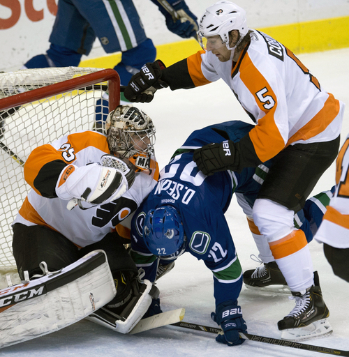 Philadelphia Flyers defenceman Braydon Coburn (5) tries to clear Vancouver Canucks left wing Daniel Sedin (22) from in front of Philadelphia Flyers goalie Steve Mason during the first period of an NHL hockey game against the Philadelphia Flyers in Vancouver, British Columbia, Monday, Dec. 30, 2013. (AP Photo/The Canadian Press, Jonathan Hayward)
