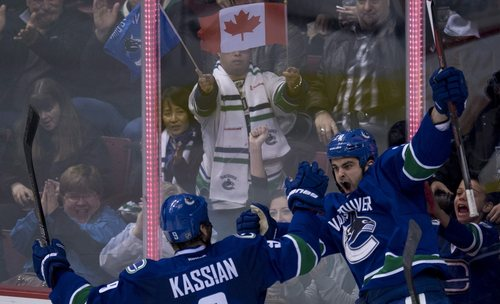 Vancouver Canucks left wing Tom Sestito, right, celebrates his goal with Vancouver Canucks right wing Zack Kassian (9) during the second period of an NHL hockey game against the Philadelphia Flyers in Vancouver, British Columbia, Monday, Dec. 30, 2013. (AP Photo/The Canadian Press, Jonathan Hayward)