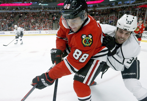 Los Angeles Kings defenseman Willie Mitchell (33) battles Chicago Blackhawks right wing Patrick Kane for the puck during the second period of an NHL hockey game Monday, Dec. 30, 2013, in Chicago. (AP Photo/Charles Rex Arbogast)