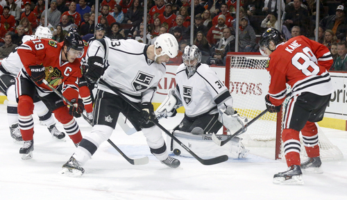 Chicago Blackhawks center Jonathan Toews (19) and right wing Patrick Kane (88) battle Los Angeles Kings defenseman Willie Mitchell (33) for the puck in front of goalie Martin Jones during the second period of an NHL hockey game Monday, Dec. 30, 2013, in Chicago. (AP Photo/Charles Rex Arbogast)