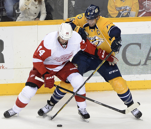 Detroit Red Wings right wing Todd Bertuzzi (44) tries to get control of the puck while being defended by Nashville Predators defenseman Shea Weber (6) in the second period of an NHL hockey game on Monday, Dec. 30, 2013, in Nashville, Tenn. (AP Photo/Mark Zaleski)