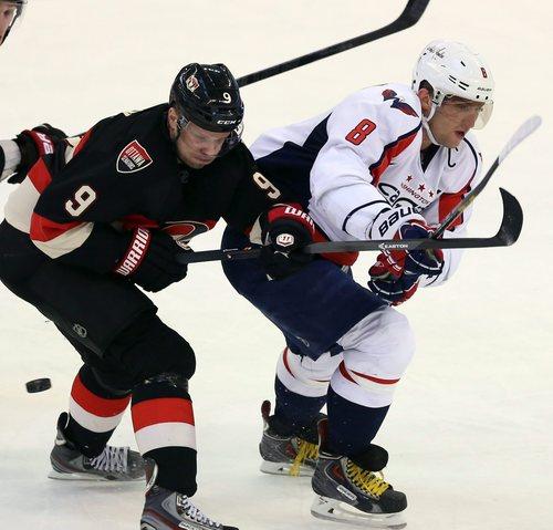 Ottawa Senators' Milan Michalek (9)checks Washington Capitals' Alex Ovechkin (8) during third period NHL hockey action in Ottawa, Ontario, on Monday, Dec. 30, 2013.  Ottawa won 3-1. (AP Photo/The Canadian Press, Fred Chartrand)