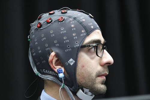 FILE - In this Feb. 17, 2011 file photo, a man sends brain-computer interface commands to a robotic computer during Science Conference at Convention Center in Washington. JWT, the global advertising and marketing company, predicts brain-computer interfaces, or BCIs, will push further into the commercial mainstream next year. (AP Photo/Jose Luis Magana, File)